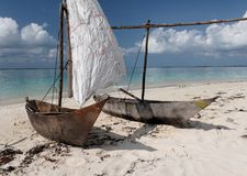 Two wooden sailing boats on tropical beach. White sail against blue sky, white clouds Stock Image