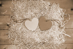 Two wooden sepia hearts in nest Stock Photography