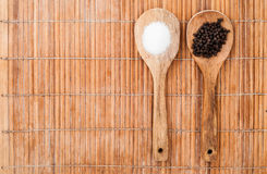 Two wooden spoon with salt and pepper. Two wood spoon with Pepper and salt on brown bamboo background Stock Image