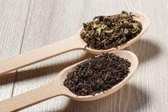 Two wooden spoons with dry leaves of black and green tea Royalty Free Stock Photography