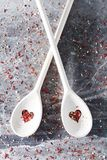 Spoons with heart-shaped holes on a messy background. Two wooden spoons with heart-shaped holes and red spice inside and all around them. Messy background Stock Photo