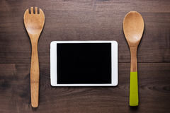 Two wooden spoons and tablet computer Royalty Free Stock Images