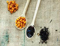 Two wooden spoons with vitaminic healthy sea buckthorn berries and black tea over sackcloth background. cooking, stock photography