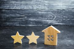Two wooden stars and a house. Two star hotel or restaurant. Review of the critic. Quality of service and level of service. Rating. Of houses and private stock photo