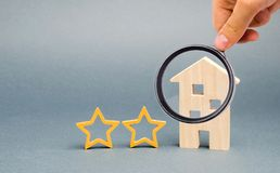 Two wooden stars and a house. Two star hotel or restaurant. Review of the critic. Quality of service and level of service. Rating royalty free stock image