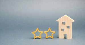 Two wooden stars and a house. Two star hotel or restaurant. Review of the critic. Quality of service and level of service. Rating. Of houses and private stock photography