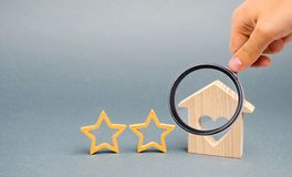 Two wooden stars and a house. Two star hotel or restaurant. Review of the critic. Quality of service and level of service. Rating. Of houses and private royalty free stock images