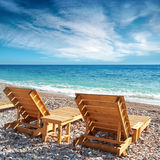 Two wooden sun loungers on the beach Stock Photo
