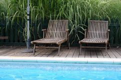 Two wooden sun loungers. By the side of a swimming pool royalty free stock photography