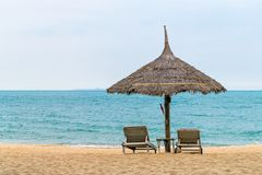 Two wooden sun loungers stand on coast of ocean stock photo