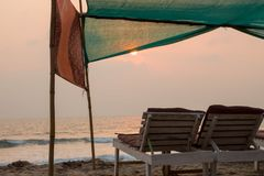 Two wooden sunbeds on the beach at sunset time. royalty free stock photos