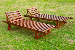 Two wooden sunbeds on the green grass lawn Stock Photography