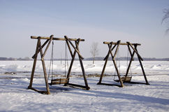Two wooden swings in winter park Stock Image