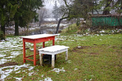 Two wooden table with autumn first snow in farm garden Royalty Free Stock Image