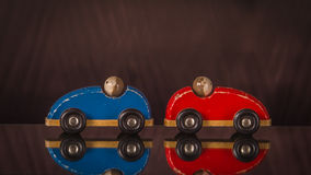 Two wooden toy cars in red and blue  with men. Stock Photos