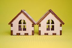 Two wooden toy house model on green background front view royalty free stock image