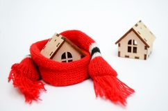 Two wooden toy houses on white background, one house weared on scarf, concept for insulation houses with copyspace stock images