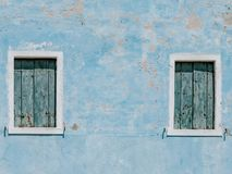 Old blue house wall with two wooden windows stock photos