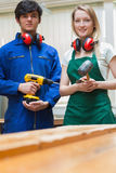 Two woodworking students standing before a workbench. Woodworking students standing before a workbench and holding a driller and a hammer Royalty Free Stock Photography