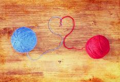 Two wool balls with heart shape over wooden board Stock Photo