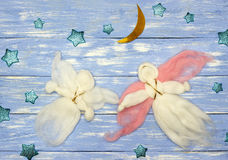 Two woolen flying angel dolls, stars and lunar month on blue wooden background Royalty Free Stock Photography