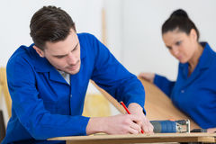 Two worker in blue dungarees in carpenters workshop. Two worker in blue dungarees in a carpenters workshop Royalty Free Stock Photo
