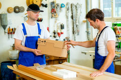 Two worker with cardboard in a carpenter's workshop Stock Photography