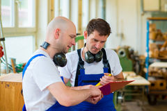 Two worker in a carpenter's workshop Royalty Free Stock Photos