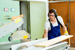 Two worker in a carpenter's workshop using saw Royalty Free Stock Photos