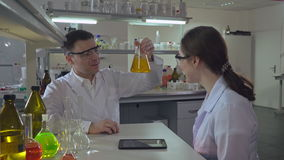 Two worker in chemical laboratory. Happy scientist teaching young assistant or student how conduct an experiment. Woman and man discussing results stock footage