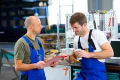 Two worker in factory in conversation Royalty Free Stock Photos