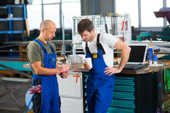 Two worker in factory in conversation Royalty Free Stock Photo