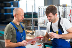 Two worker in factory in conversation Stock Images