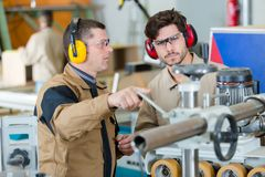Two worker in factory on machine stock photos