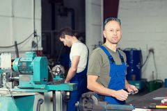 Two worker in factory. On work bench Stock Image