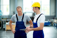Two worker in factory using tablet pc Stock Images