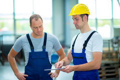 Two worker in factory using tablet pc Stock Image