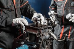 Two worker, the mechanic installs a new piston. Disassemble engine block vehicle. Motor capital repair. Sixteen valves Royalty Free Stock Photography