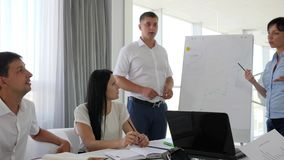 Two worker beside whiteboard discussing business development into diagram form. In conference room stock video footage