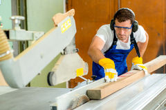 Two worker in workshop using saw machine. Worker in a carpenter's workshop using saw machine Stock Photo