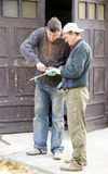 Two workers. Busy with something, they are holding a tool in their hands and struggling with it Royalty Free Stock Image