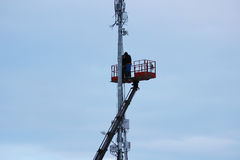 Two workers assemble equipment for telecommunications on the tower with the help of the lift in the winter Royalty Free Stock Images