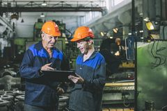 Free Two Workers At An Industrial Plant With A Tablet In Hand, Working Together Manufacturing Activities Stock Photo - 100341400