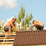 Two workers attach roof skate. Royalty Free Stock Photo
