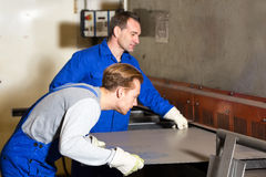 Two workers bending sheet metal with large machine. Two workers bending sheet metal with a large machine Royalty Free Stock Photography