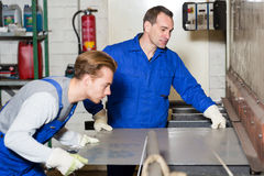 Two workers bending sheet metal with large machine Royalty Free Stock Photo