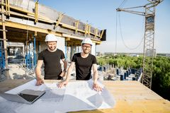 Workers with drawings at the construction site. Two workers in black t-shirts and protective harhats working with drawings at the construction site outdoors stock image