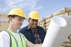 Two Workers With Blueprint At Site Royalty Free Stock Photos