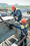 Two workers busy on bridge construction Stock Photos