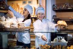 Two workers cafe offering fancy cakes for sale Stock Photo